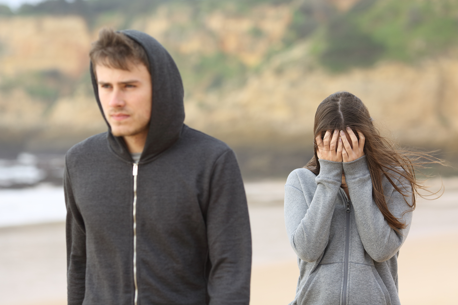 Teenager couple breaking up. The angry boyfriend leaves his sad girlfriend